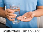 man holding pill and glass of... | Shutterstock . vector #1045778170
