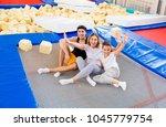 family in trampoline center | Shutterstock . vector #1045779754