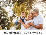 happy mom and dad hold little... | Shutterstock . vector #1045794853