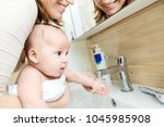 Small photo of Mother wahing baby hand . Child get accustom for cleanness. Mom and son having fun together in bathroom. Hygiene and healthcare for children.