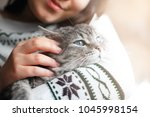 smiling woman at home holding... | Shutterstock . vector #1045998154