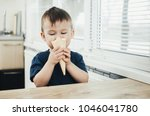 Small photo of A child in a dark-blue t-shirt in the bright kitchen eating a waffle ice cream cone in the summer house