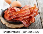 Hot fried bacon pieces in a...