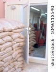 Small photo of Pile of sacks with pellets and pellet burner