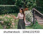 a girl is walking in a blooming ... | Shutterstock . vector #1046131933