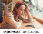 Young woman sitting at table in cafe looking at phone being unhappy with breakup.