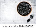 Small photo of Fresh dry prunes on white rustic table. Dried plums in wooden bowl, top view on white of prune.