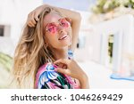 Close-up portrait of magnificent caucasian girl in round pink sunglasses. Lovable long-haired blonde woman enjoying life and having fun at resort.