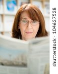 Portrait of middle aged woman with eyeglasses reading paper in library - stock photo