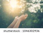 woman open hand up to sunset... | Shutterstock . vector #1046302936
