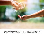 water pouring in woman hand on...   Shutterstock . vector #1046328514