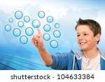 Portrait of Boy pointing at web icons with futuristic interface. - stock photo