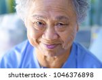 Small photo of Asian senior or elderly old lady woman patient smile bright with strong health while sitting on bed in nursing hospital : healthy strong medical concept