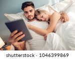 young couple lying in bedroom... | Shutterstock . vector #1046399869