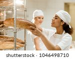 female baker putting fresh... | Shutterstock . vector #1046498710