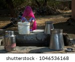 a woman fetching water from... | Shutterstock . vector #1046536168