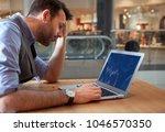 depressed investor analyzing... | Shutterstock . vector #1046570350