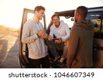 three male friends on a road... | Shutterstock . vector #1046607349