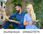 Small photo of Romantic vintage date concept. Couple in love sit back to back outdoor, nature background. Romantic couple holds old book with poems about love. Couple with smiling faces reading poems.