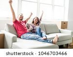 couple sitting together on sofa ... | Shutterstock . vector #1046703466