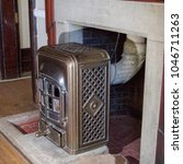 Small photo of Antique anthracite heater in bronze with micah windows set in old stone fire place