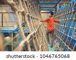 young asian boy climbing rope... | Shutterstock . vector #1046765068