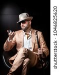 Small photo of Dandy man dressed as mafia boss, pimp or playboy looks at himself in the pocket mirror, wearing sunglasses, white hat and pink or peach suit, sitting in a leather chair, isolated on black background