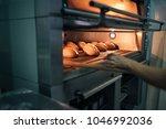 baker making bread at a bakery. ... | Shutterstock . vector #1046992036