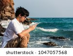 asian man using phone typing...   Shutterstock . vector #1047057568