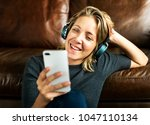 a woman listening to the music | Shutterstock . vector #1047110134