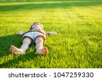 the boy lies on a well groomed...   Shutterstock . vector #1047259330
