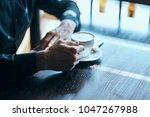 a cup of coffee in hand         ...   Shutterstock . vector #1047267988