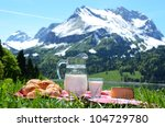 Milk, cheese and bread served at a picnic on Alpine meadow, Switzerland - stock photo