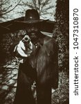 Small photo of Cowboy in a duster jacket and cowboy hat pointing a gun at the camera. Edited with vintage film effects.Cowboy in a duster jacket and cowboy hat pointing a gun at the camera. Edited with vintage film