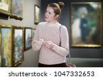 Stock photo portrait of young woman with a guide looking at pictures at museum of arts 1047332653