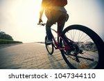 cyclist riding mountain bike in ... | Shutterstock . vector #1047344110