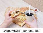 fast food on the table and hand ... | Shutterstock . vector #1047380503