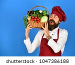 Small photo of Handsome young chef with a basket of green groceries standing on blue background. Cooking and vegetarian diet concept