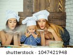 women and child blowing flour.... | Shutterstock . vector #1047421948