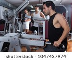 sporty guy training muscles of... | Shutterstock . vector #1047437974
