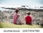family sitting looking out to... | Shutterstock . vector #1047454780