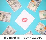 Small photo of Dollars, white paper with red lips print. Banknotes on a blue background. Love for money.