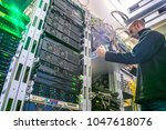 the engineer installs the new... | Shutterstock . vector #1047618076