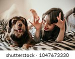 Stock photo little young girl making funny faces to her dog on the bed in modern bedropm decorated with grey 1047673330