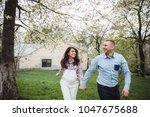 happy couple hold hands running ... | Shutterstock . vector #1047675688