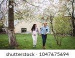 happy couple hold hands running ... | Shutterstock . vector #1047675694