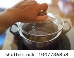 pot lid in hand with blur of... | Shutterstock . vector #1047736858