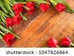 Small photo of Red tulips are lying diagonally on opposite diagonal rustic wooden background with central copy space.
