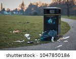 Small photo of The litter bin in public park and litter around .