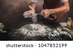 man preparing buns at table in... | Shutterstock . vector #1047852199